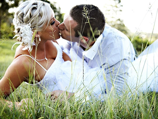 Couple kissing in the grass at Riverside Oakes wedding venue