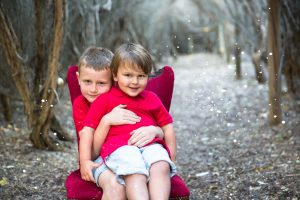 Two bothers cuddling on red chair for there Christmas Photos at Catherine Hill Bay